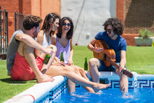 Cheerful Young Men And Women Sitting With Guitar And Beer Bottles At Poolside On Sunny Day