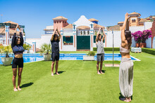 Young Multi-ethnic Male And Female Friends Practicing Yoga At Lawn In Back Yard During Sunny Day