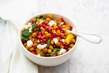 Bowl Of Vegetarian Salad With Chick-peas, Turmeric, Bell Peppers, Tomatoes, Parsley, Feta Cheese And Pomegranate Seeds