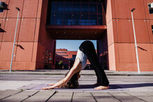Young Woman Performing Yoga In Downward Facing Dog Position On City Street