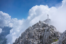 Low Angle View Of Religious Cross On Mountain Top Against Cloudy Sky, Bergamasque Alps, Germany