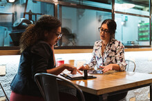 Young Businesswoman Pointing At Diary While Planning With Female Entrepreneur In Coffee Shop