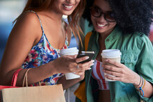 Girlfriends With Coffee To Go Using Smartphone