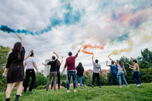 Carefree Friends Playing With Smoke Bombs Against Cloudy Sky In Park