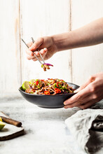 Fried Rice Noodles With Vegetables, Pad Thai Style With Boys Hand Holding Chopsticks