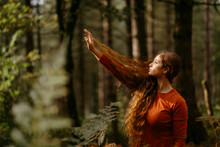 Beautiful Woman With Long Blond Hair Looking Away While Standing Against Trees In Forest
