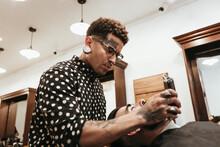 Fashionable Barber Styling Man's Beard At Salon