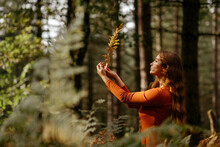 Young Woman With Long Hair Holding Plant While Standing Against Trees In Forest