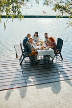 Friends Having Dinner On Jetty At A Lake