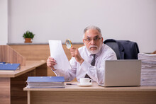 Old Male Employee Reading Paper In The Office
