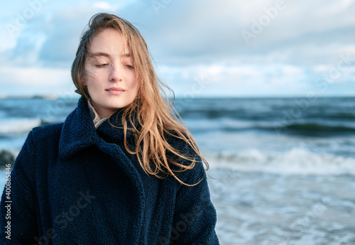 Tela Portrait of Young beautiful woman braving a cold winter day at the seaside