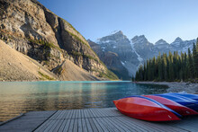 Canada, Alberta, Banff, Kayaks On Jetty On Moraine Lake Surrounded With Mountains