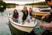 Family Looking At Woman Anchoring Boat Near Pier During Sunset
