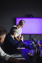 Male IT Professional Pointing At Projection Screen By Female Colleague At Workplace