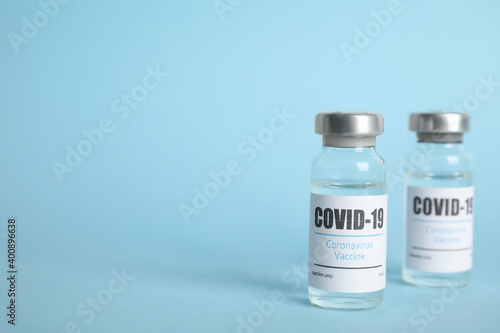 Tableau sur Toile Vials with coronavirus vaccine on light blue background, space for text
