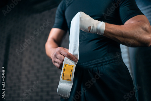 Fotografie, Obraz athletic boxer man bandage hand and preparing for training or fighting in gym