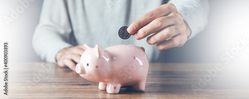 Fotografija man hand coins with piggy bank on desk