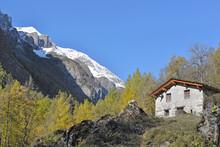 Traditional Alpine Cottage In Mountain Landscape Under Blue Sky