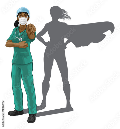 Obraz Nurse or doctor super hero woman in surgical or hospital scrubs with stethoscope and mask PPE. Pointing at viewer in a we need or want you gesture. Revealed as a superhero by the shape of her shadow. - fototapety do salonu