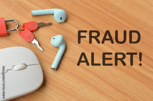 Canvas Print Selective focus of computer mouse, earphones, padlock and keys over wooden background written with text FRAUD ALERT!