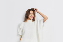 Atmosphere. Portrait Of Beautiful Brunette Woman In Comfortable Soft Longsleeve Isolated On White Studio Background. Home Comfort, Emotions, Facial Expression, Winter Mood Concept. Copyspace.