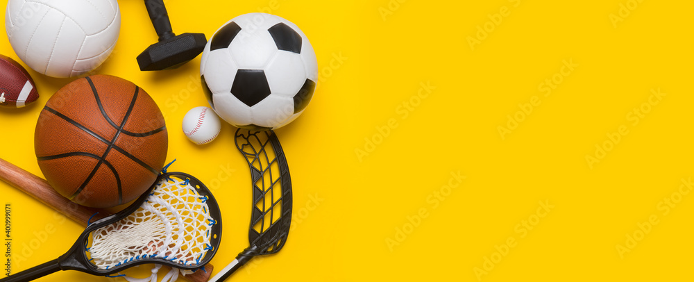 Obraz Assorted sports equipment including a soccer ball, volleyball, baseball, american football, lacrosse and hockey on a blue background. Top view, space for your text fototapeta, plakat