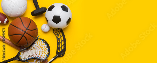 Fototapeta Assorted sports equipment including a soccer ball, volleyball, baseball, american football, lacrosse and hockey on a blue background. Top view, space for your text obraz