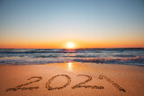Fototapeta Kawa jest smaczna - Happy New Year 2021 concept, lettering on the beach. Written text on the sea beach at sunrise.