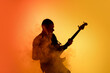 Smoke. Silhouette of young male guitarist isolated on orange gradient studio background in neon light. Beautiful shadow in action, performing. Concept of human emotions, expression, ad, music, art.