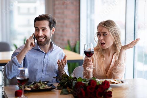 Fotografia Millennial man talking on cellphone on romantic date at cafe, his girlfriend fee
