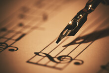 Writing Musical Notes On Sheet With Quill Pen And Ink. Music Education. Closeup