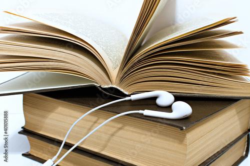 Slika na platnu audio headphones on stack of old yellowed hardback books
