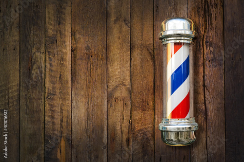Barber pole. Barbershop pole on a wooden background with copy space. - fototapety na wymiar
