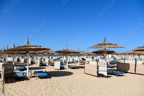 Fotografie, Obraz Sun loungers on the sea sandy beach