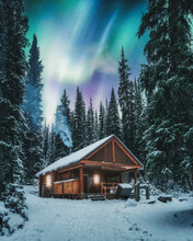 Aurora Borealis Over Wooden Cottage With Smoke On Snow In Pine Forest At Yoho National Park