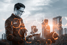 Eastern Young Businessman Looking Into His Notebook To Achieve Tremendous Growth In Business Based On Technologies. Worldwide Process To Conduct Transactions. Tech Hologram Icons Over Bangkok