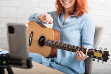 Caucasian Woman Playing Guitar Live On A Smartphone. The Girl Leads A Music Video Blog