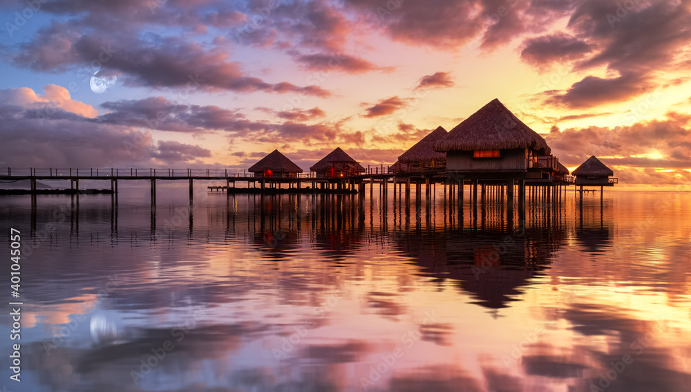 Fototapeta Tahiti bungalows with reflection in water during sunset