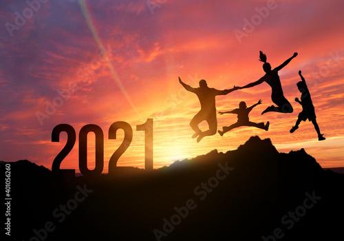 Tablou Canvas Silueta de familia levanta las manos y salta al hermoso cielo dorado con el texto de fondo 2021