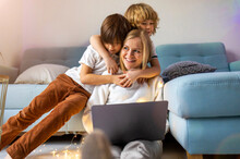 Young Mother Trying To Work From Home With Her Kids As A Company