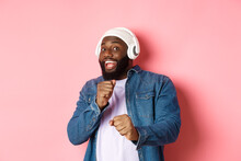 Happy African-american Man Dancing, Listening Music In Headphones And Looking At Camera, Standing Over Pink Background