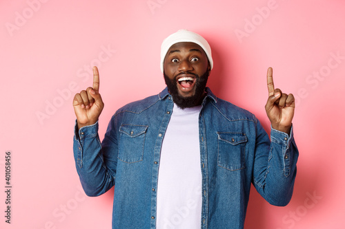 Fényképezés Cheerful Black man showing fantastic promo offer, pointing fingers up and smilin
