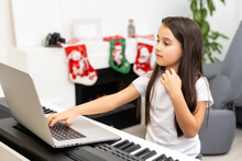 Christmas Time, Laptop On Piano Keys, Little Girl Playing Piano