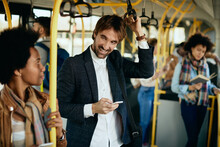 Happy Man Using Cell Phone And Talking To A Passenger While Commuting By Bus.