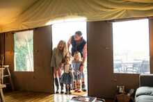 Happy Family Arriving In Yurt Cabin Doorway
