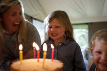 Happy Mother And Daughter Celebrating Birthday With Cake And Candles