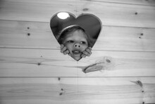 Cute Girl Peering Through Heart Shape In Wood