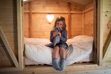 Cute Girl Playing With Stuffed Bunny On Bed In Wood Loft