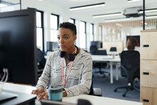 Businesswoman Working At Computer In Open Plan Office