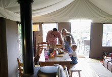 Happy Family At Dining Table With Strawberry Cake On Yurt Tent